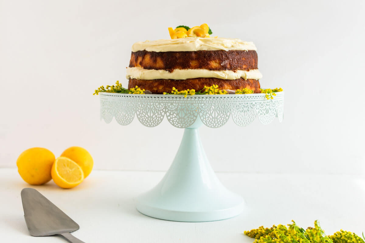 Lemon ricotta cake with cream cheese on a cake stand with lemons in the back, flowers, and a cake knife.