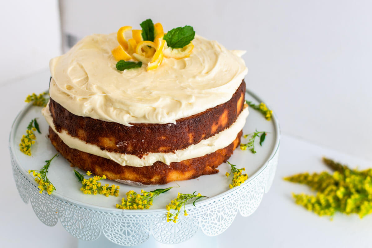A lemon ricotta cake on a cake stand garnished with lemon swirls and mint with yellow flowers spread around the cake.