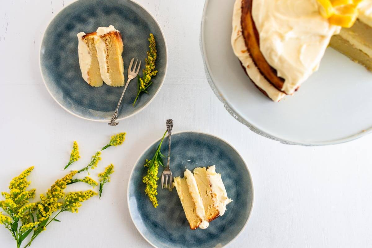 2 slices of lemon ricotta cake on a plate with the who cake on the side and yellow flowers on the opposite side.