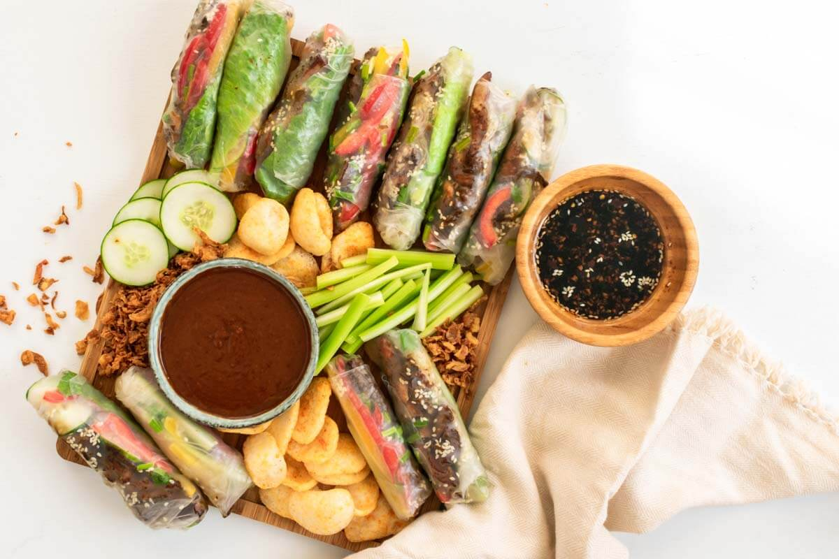 A summer roll platter with peanut sauce, Asian sauce, prawn crackers, celery, and cucumbers with a beige linen napkin on the side.