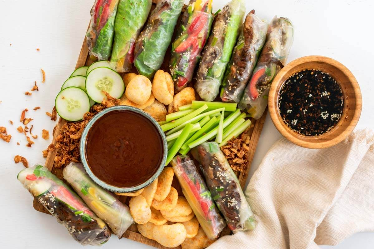 A summer roll platter with peanut sauce, Asian sauce, prawn crackers, celery, and cucumbers with a beige linen napkin on the side