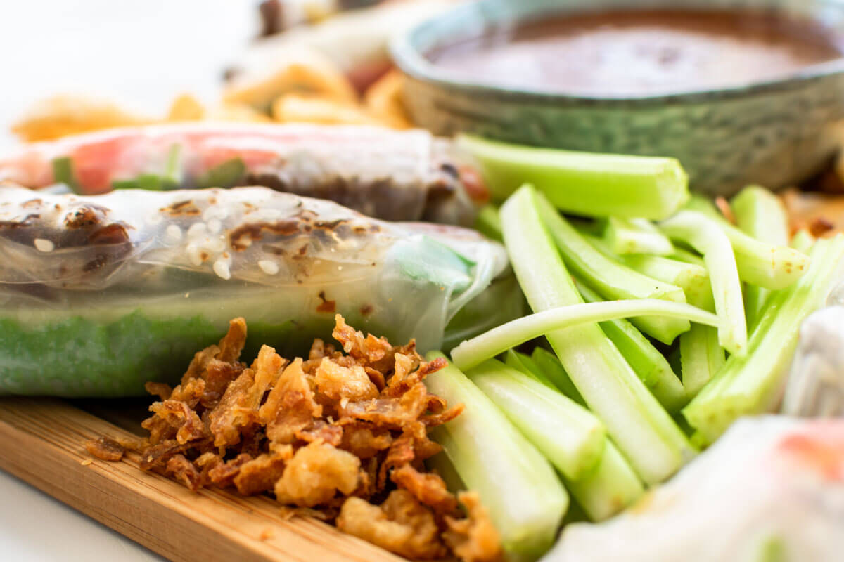A summer, fried onion, and celery stalk on a summer roll platter