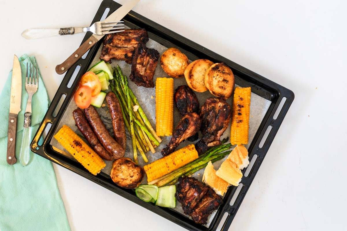 A mix grill platter with 2 forks and knives and an aqua napkin.