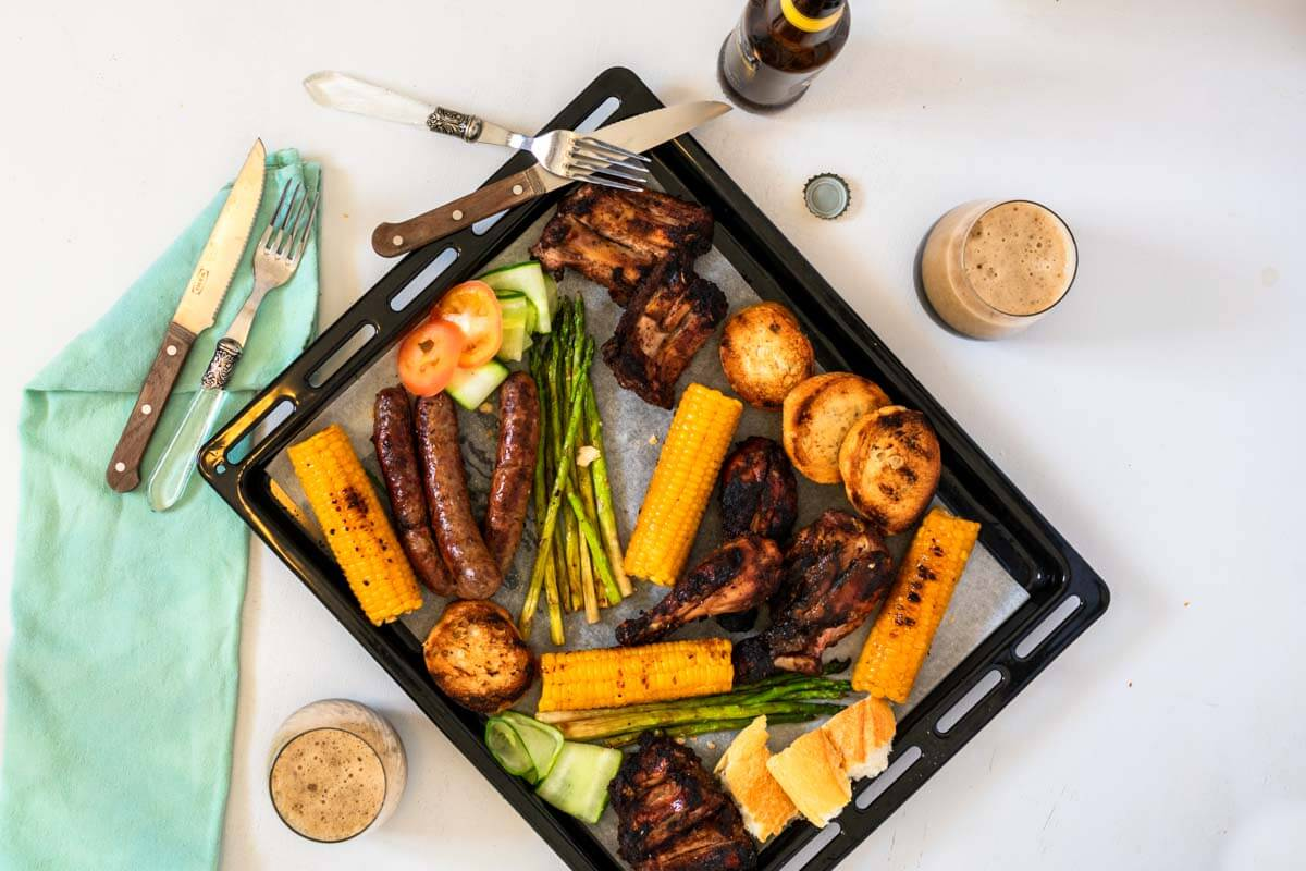 A mix grill platter with 2 forks and knives and an aqua napkin. Also 3 glasses of beer and a bottle of beer on the side.