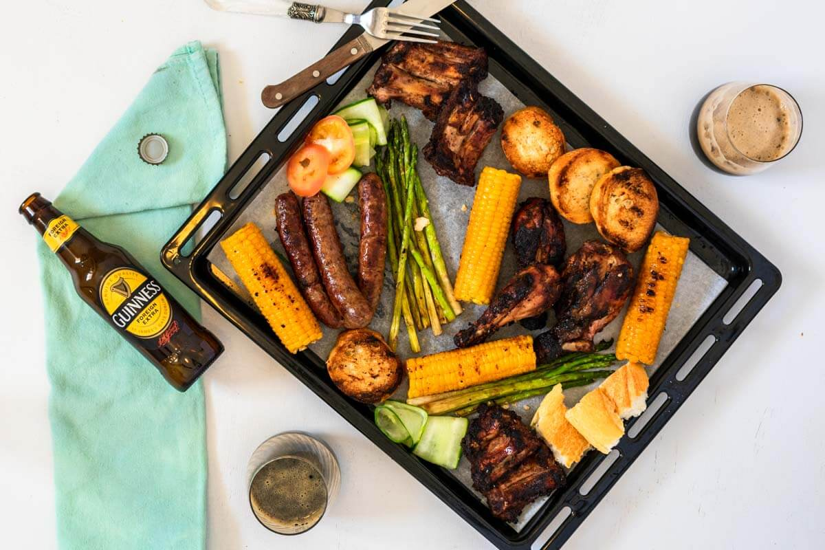 A mix grill platter with a fork, knive, and napkin plus 2 glasses of beer and a beer bottle laid flat.