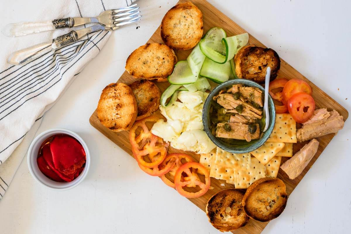A tuna platter with vegetables, bread, and crackers with a white napking on the side and two forks.