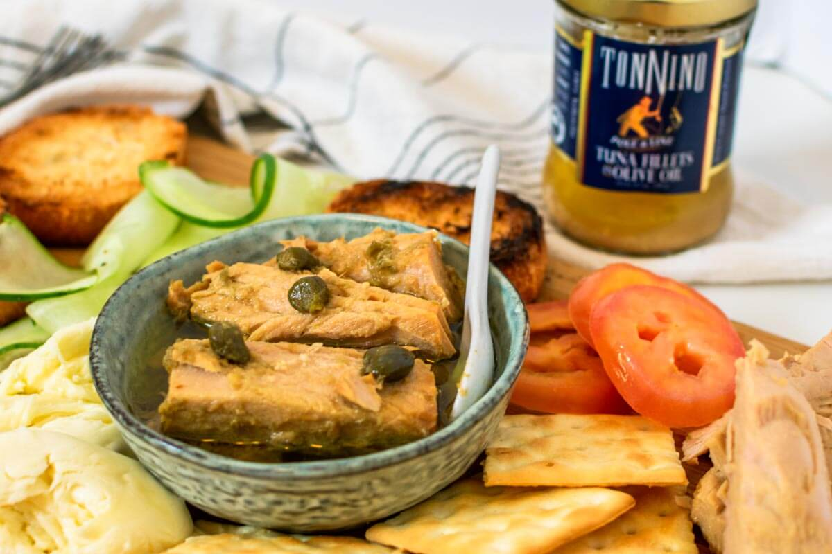 A tuna platter with vegetables, bread, and crackers with a white napkin, and a Tonnino Tuna jar.
