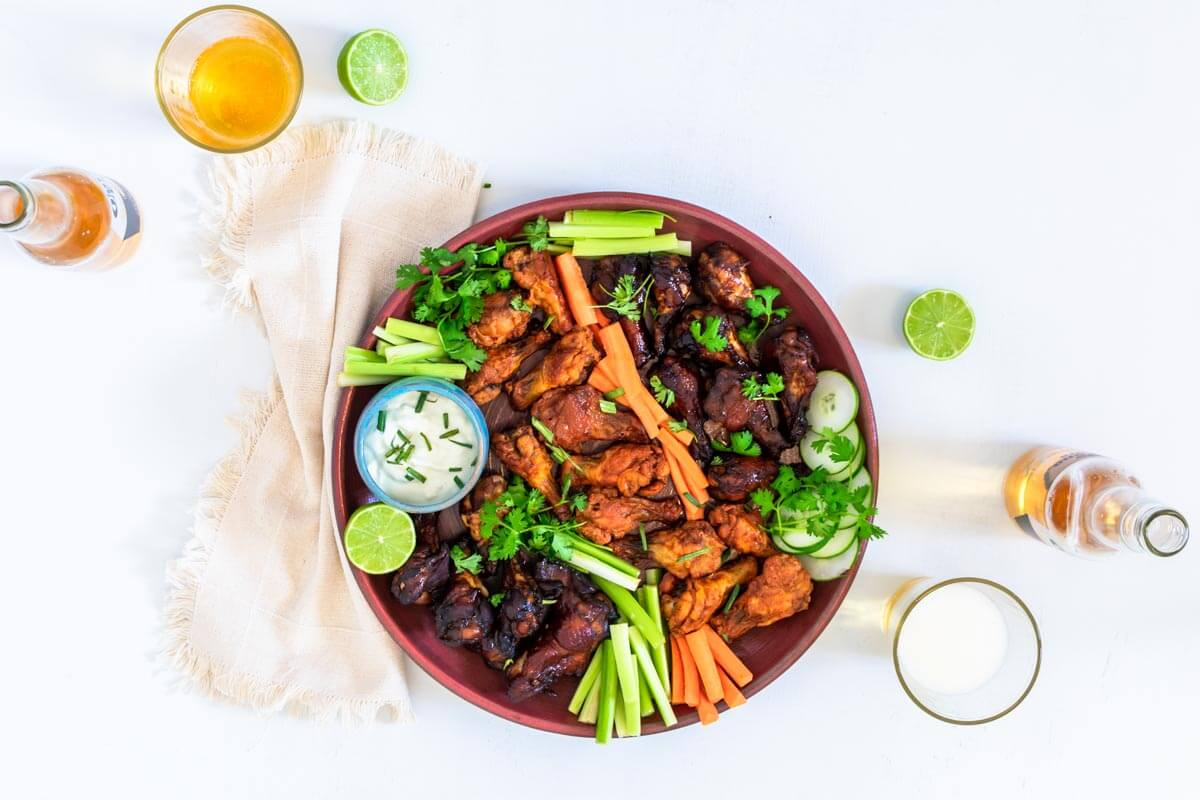 A round pink serving platter with baked chicken wings on it, veggies, and blue cheese dip. On the side 2 glasses with beer, a beige napkin, and two limes.
