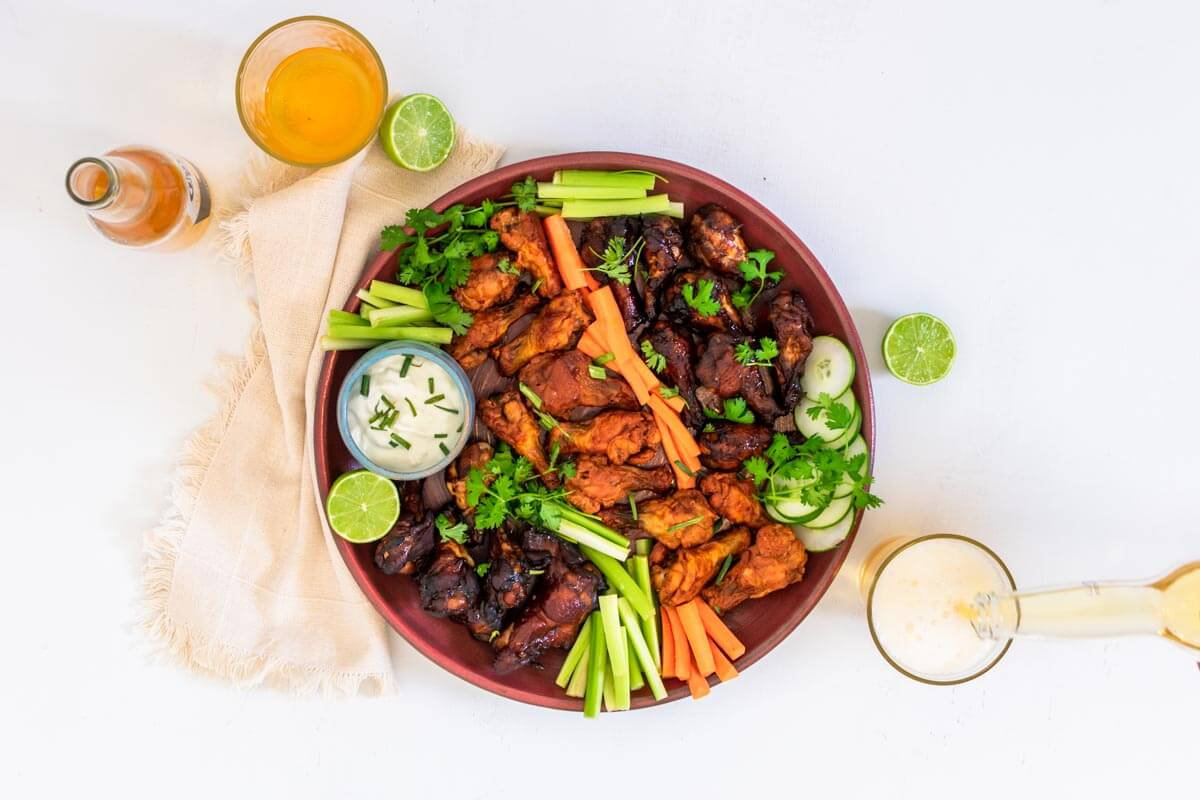 A round pink serving platter with baked chicken wings on it, veggies, and blue cheese dip. On the side 2 glasses with beer, a bottle of beer, a beige napkin, and two limes.