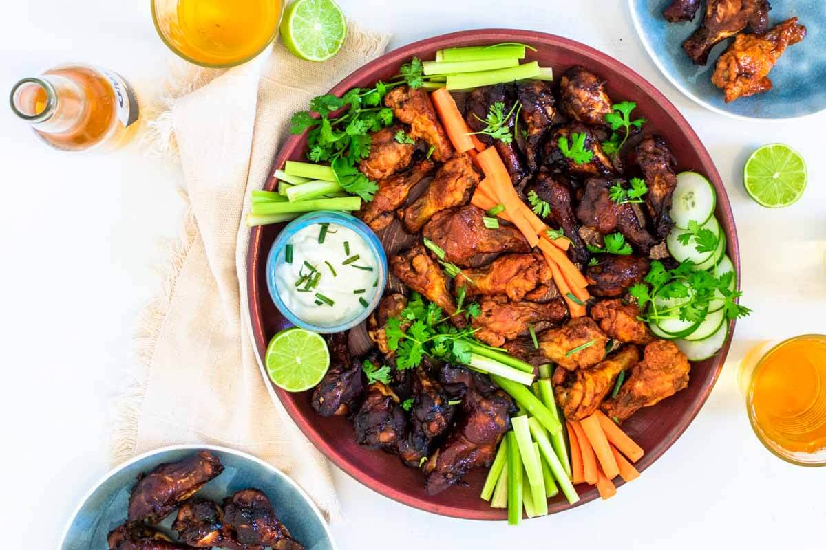 A round pink serving platter with baked chicken wings on it, veggies, and blue cheese dip. On the side 2 glasses with beer, a bottle of beer, a beige napkin, and two limes. Also two plates with wings on it.