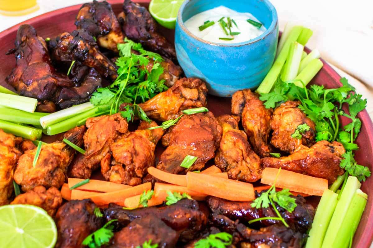various chicken wings on a platter with veggies and, garnished with coriander and a pinch bowl with blue cheese dip.