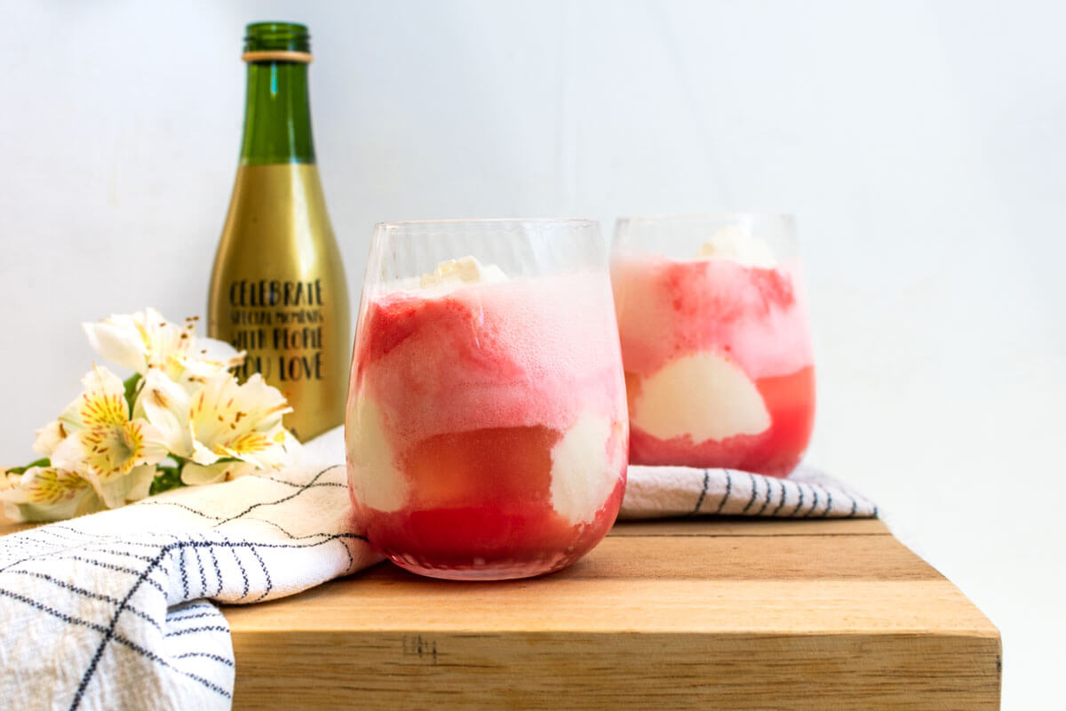 2 glasses of red champagne float with a mini champagne bottle in the back and a black and white striped napkin on the side.
