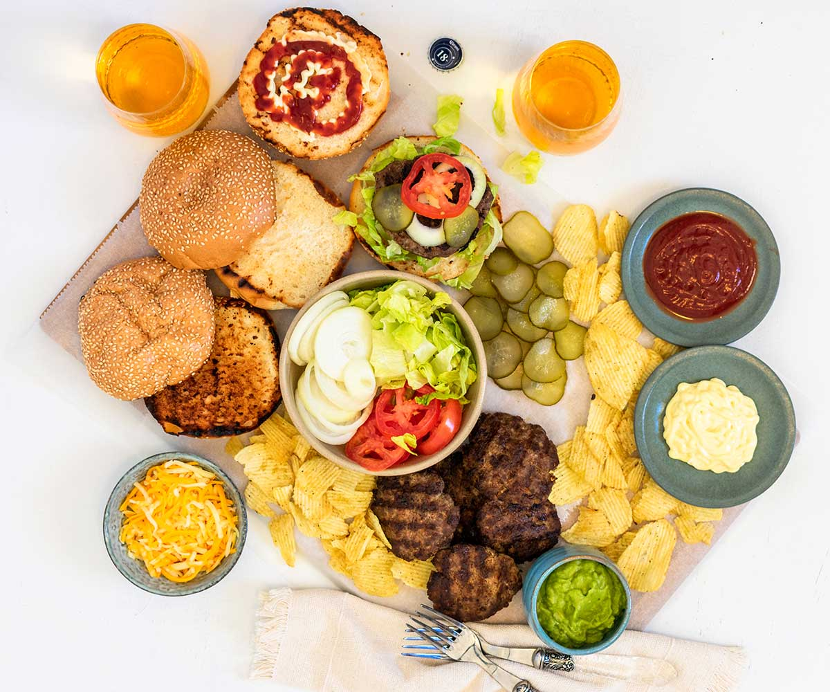 A build-your-own burger platter with 2 glasses of beer.