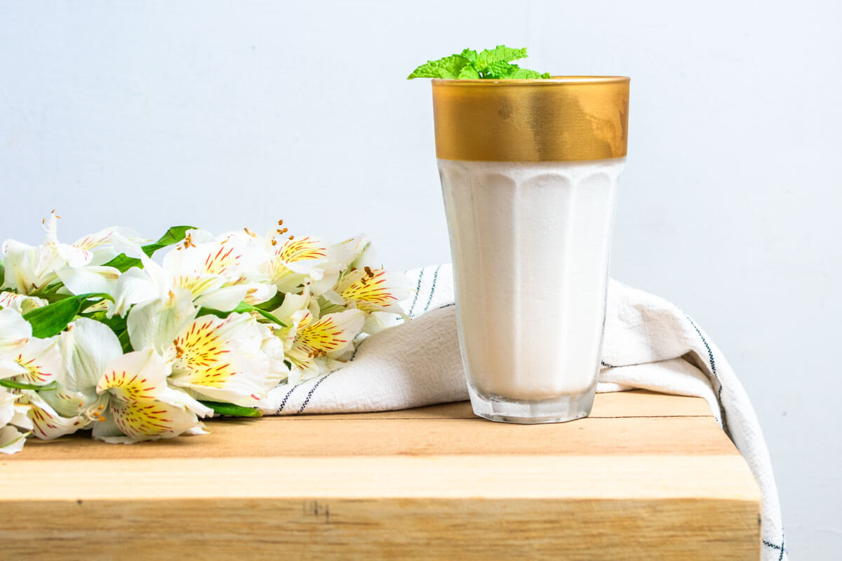 A glass of Limonada de Coco on a wooden surface with some white flowers on the left and a white and black napkin wrapped around the back of the glass.