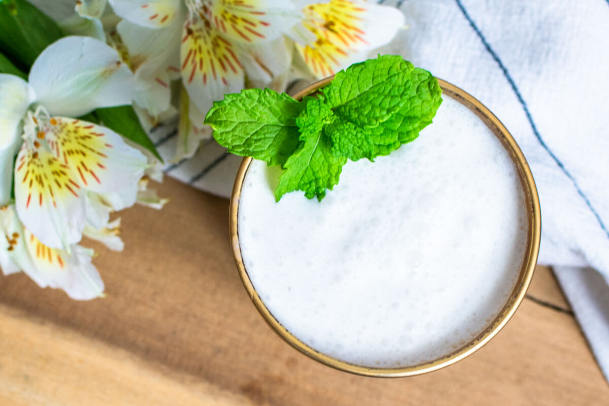 A glass of Limonada de Coco shot from above and garnished with mint leaves. White flowers on the left upper corner.