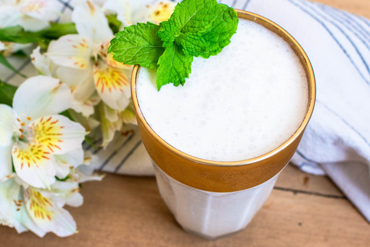 A glass of Limonada de Coco shot on 45 degree angle and garnished with mint leaves. White flowers on the left upper corner and a black and white striped napkin.