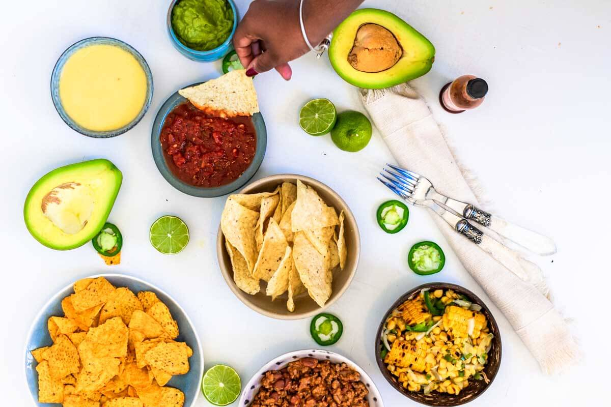 A nachos dip platter with two bowls of nachos and bowls of different dip. Lime pieces and jalapeño slices spread across and half-open avocados. Two forks and a beige napkin on the right. A hand dipping a nacho into a salsa.