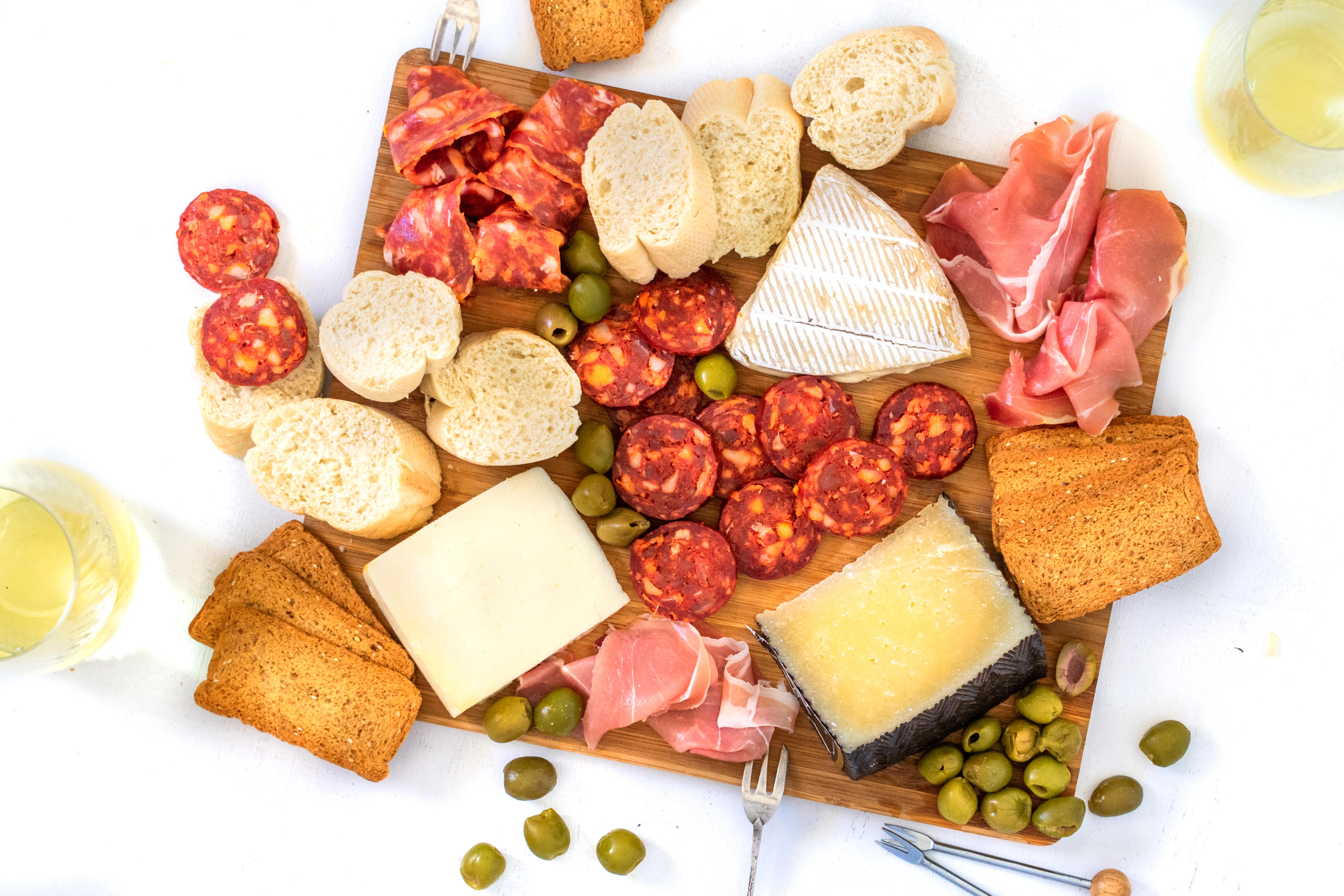 A platter with cheese, cured meat, bread, crackers, and olives.