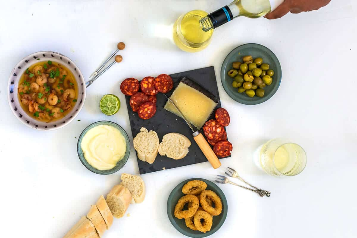 A Spanish tapas platter on a white background with a wine poured in a glass.