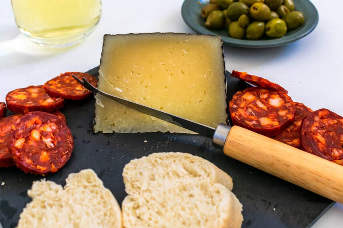 A Manchego on a Spanish tapas platter being sliced.