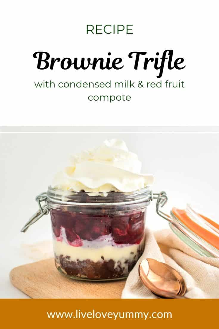 A jar with brownie trifle with condensed milk, red fruit compote, and whipped cream. Placed on a wooden board with a napkin wrapped around and rose gold spoons.