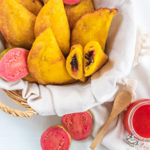 A basket of guava empanadas with fresh guavas spread across the basket an a jar of guava jam