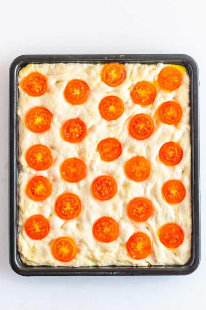 Unbaked focaccia dough with cherry tomatoes in half lined on top of it.