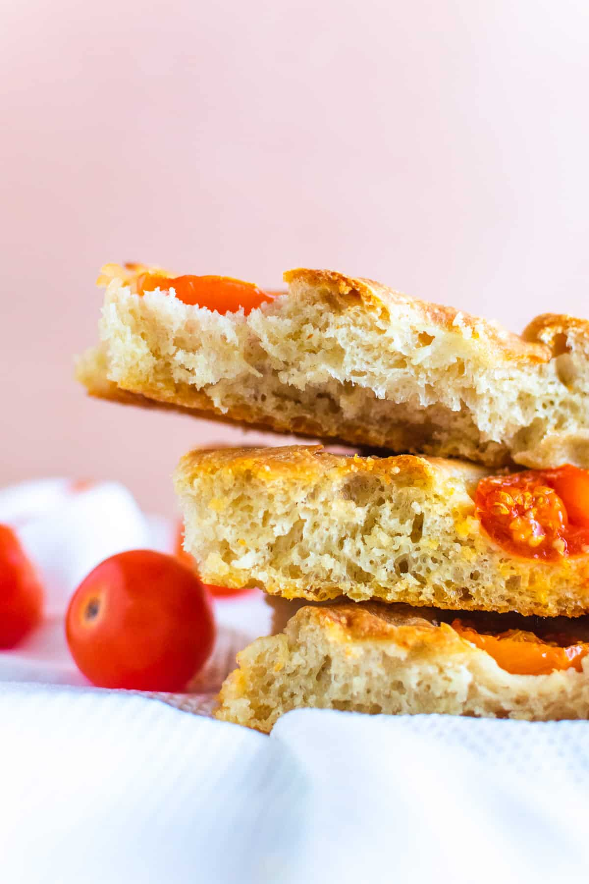 Tomato focaccia pieces inspired by salt fat acid heat stacked on top of each other.