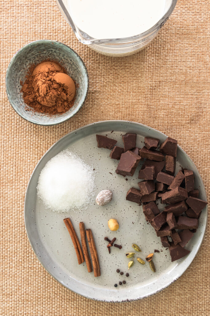A plate with chocolate chnks, chai spice mix, and remaining ingredients for hot chocolate