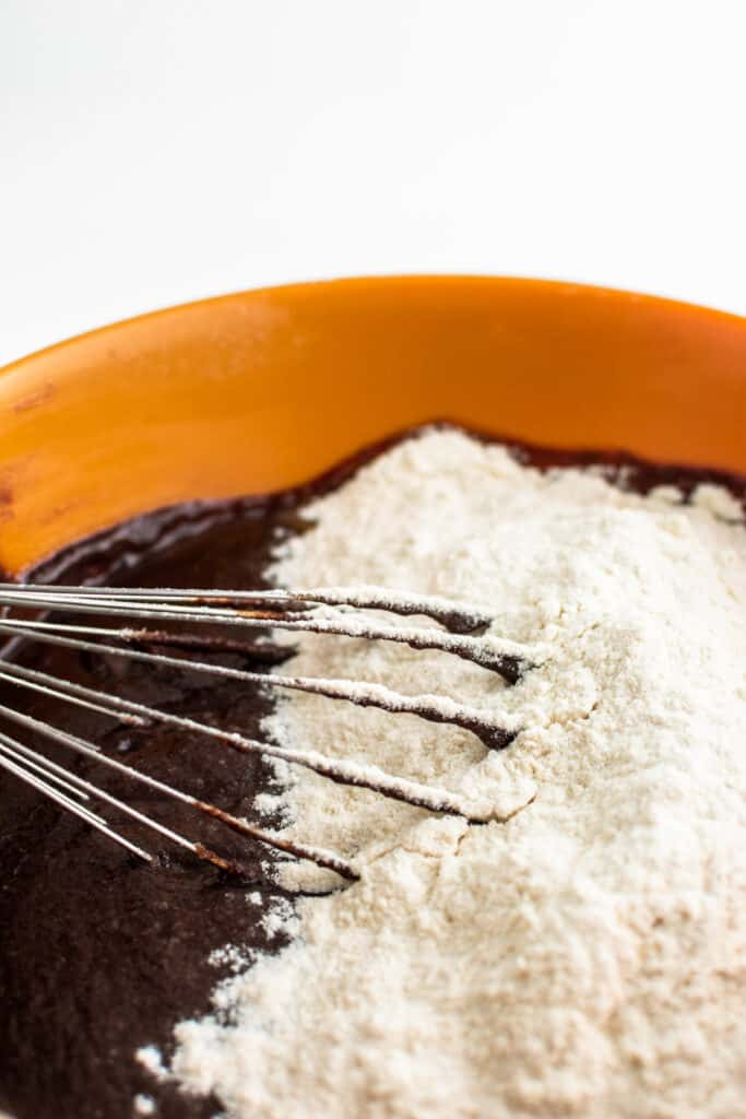 A bowl of chocolate mixture for brownie being whisked with flour.