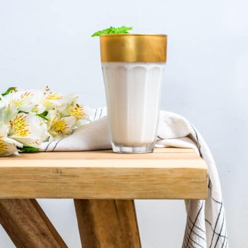 A glass of Limonada de Coco on a wooden table with some white flowers on the left and a white and black napkin wrapped around the back of the glass.