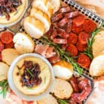 A spanish cheese & charcuterie board with dips, bread, and cured meats.