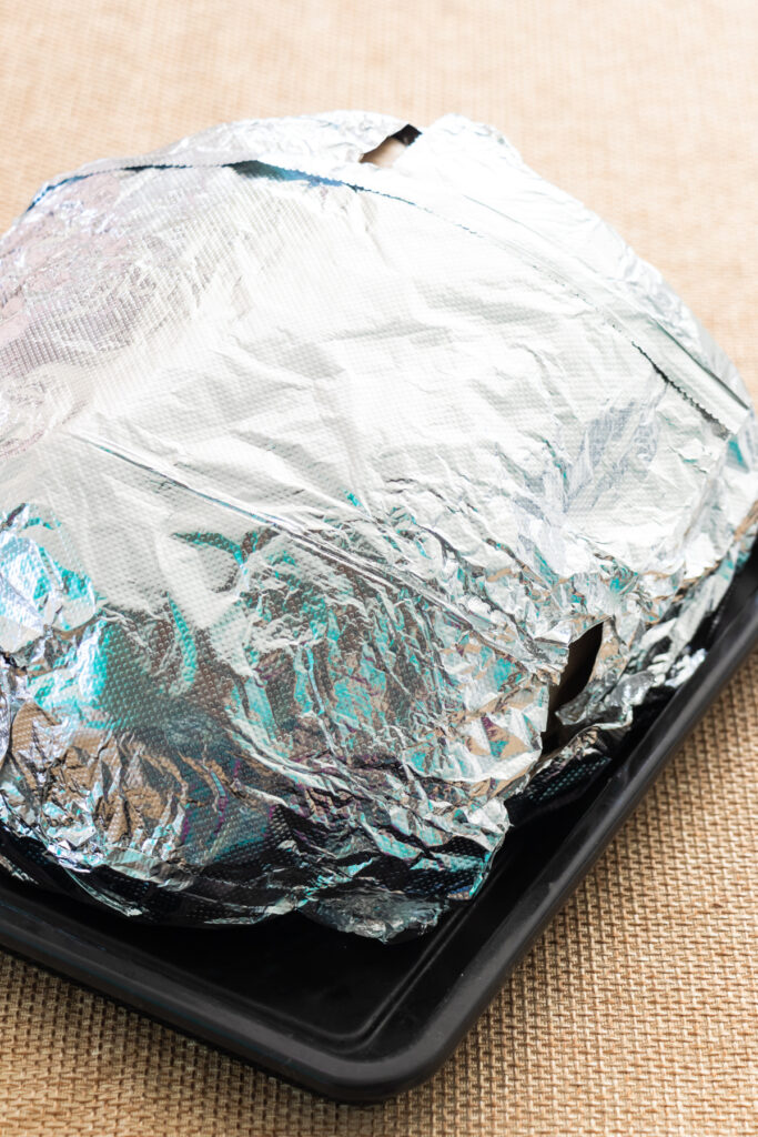 A precooked, bone-in, ham in roasting bag and wrapped with tin foil