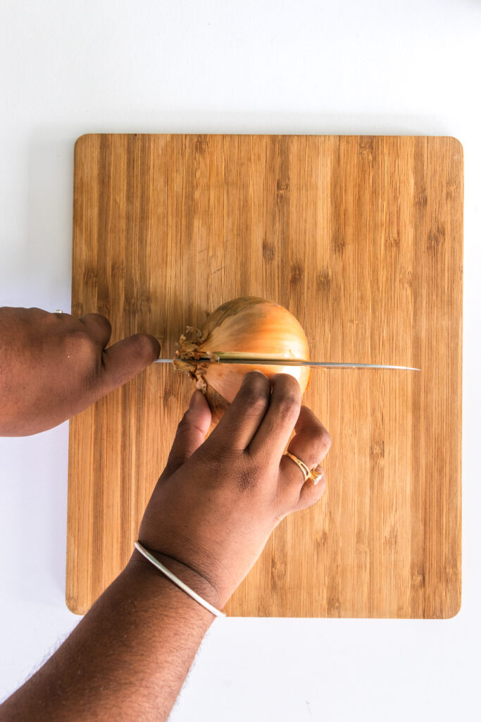 Full onion being sliced in half