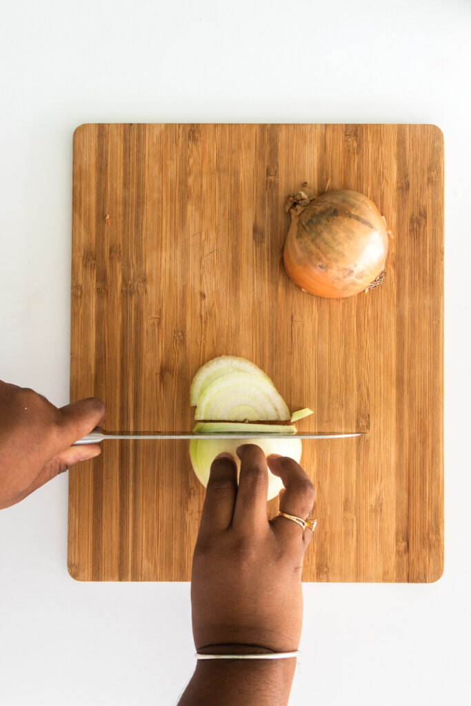 Half onion being sliced in half moon shapes