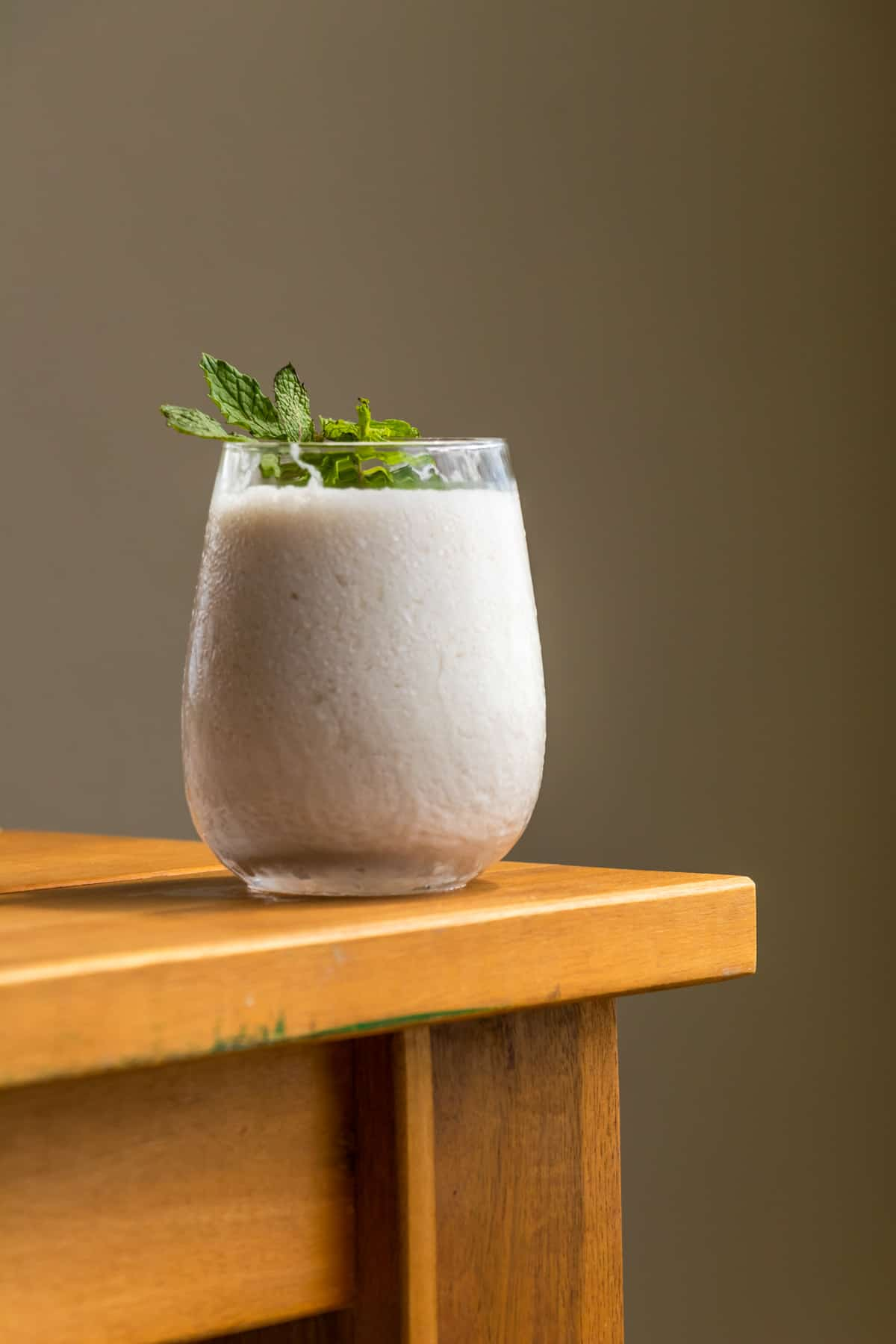 A glass of limonada de coco garnished with fresh mints on a wooden table.